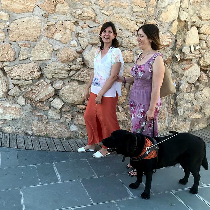 La consultora Andrea Granell acompanyant una dona amb ceguesa i el seu gos pigall. Al darrera, torre de pedra d'estructura circular, és la Torre Blava-Espai Guinovart situada al Passeig Marítim de Vilanova i la Geltrú.