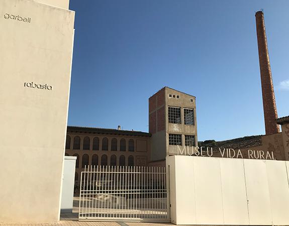 Reixa de l'entrada i façana blanca llisa del museu. En segon pla, edifici i xemeneia d'arquitectura industrial.