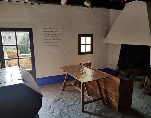 Cuina de casa de pagès del segle dinou amb una porta i una finestra petita, una taula de fusta amb un porró al centre i una llar de foc.