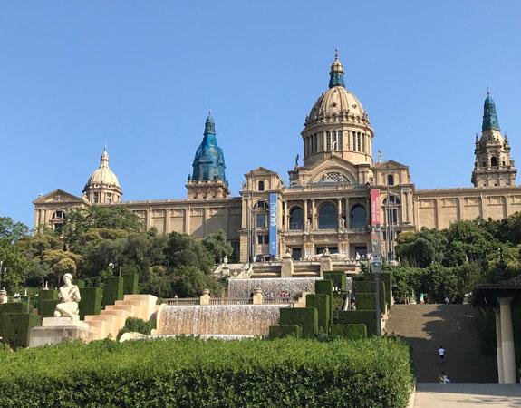 Zona ajardinada, fonts, escales i façana del Palau Nacional de Montjuïc. La façana principal és simètrica amb un cos central que sobresurt, coronat per una cúpula d'estil romà, i dos laterals amb dues cúpules més petites.