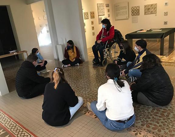Joves asseguts en rotllana en el terra enrajolat del Museu Can Tinturé dialogant després de fer una activitat sensorial.